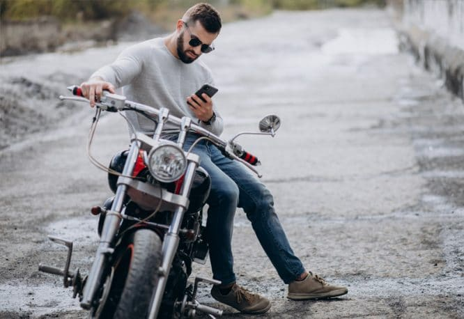 motorkár sediaci na motorke s mobilom v ruke