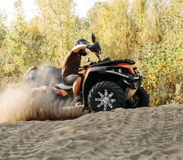 muž na štvorkolke jazdiaci v piesku